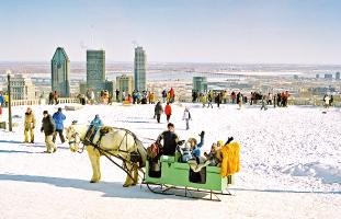 © Tourisme Montréal, Stéphan Poulin 公園の頂上から見える風景と冬を楽しむ人々