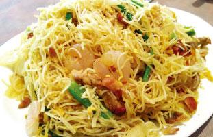 ◀Singapore Noodle 細いライスヌードルをエビ、ブタ、たっぷりの野菜と炒めた一品。あっさり塩味といった感じだか、ほのかなカレー風味とチリが隠し味。辛いものが好きな人はチリとの相性抜群なのでたっぷりチリを掛けて食べてみよう。辛いものが好きな人も苦手な人も食べられるのが◎。 Congee Wong 10 Ravel Rd. / 416-493-8222 congeewong.com