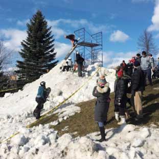 小さなな公園にジャンプ台を設置してスノーボードで遊ぶ子供達。