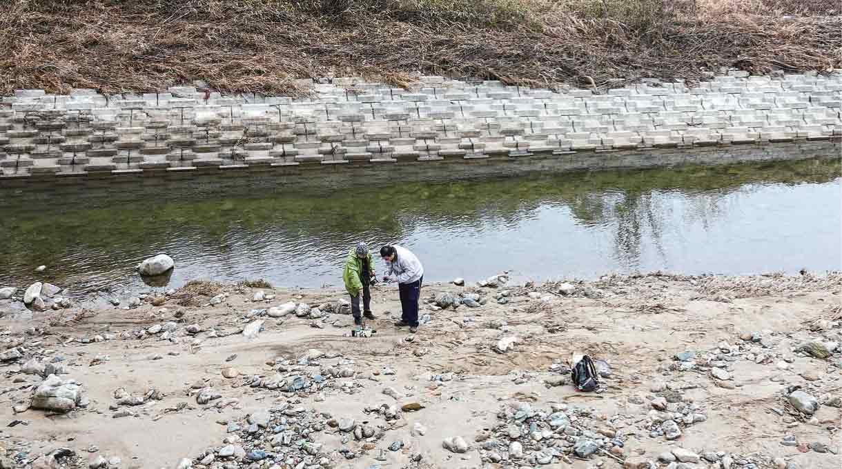 川辺でサンプル採取する田崎氏と助手の湧島氏
