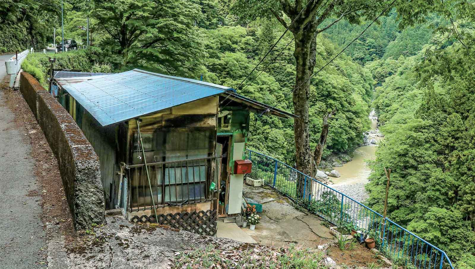 正面に渓谷、裏は道路トタン屋根の民家