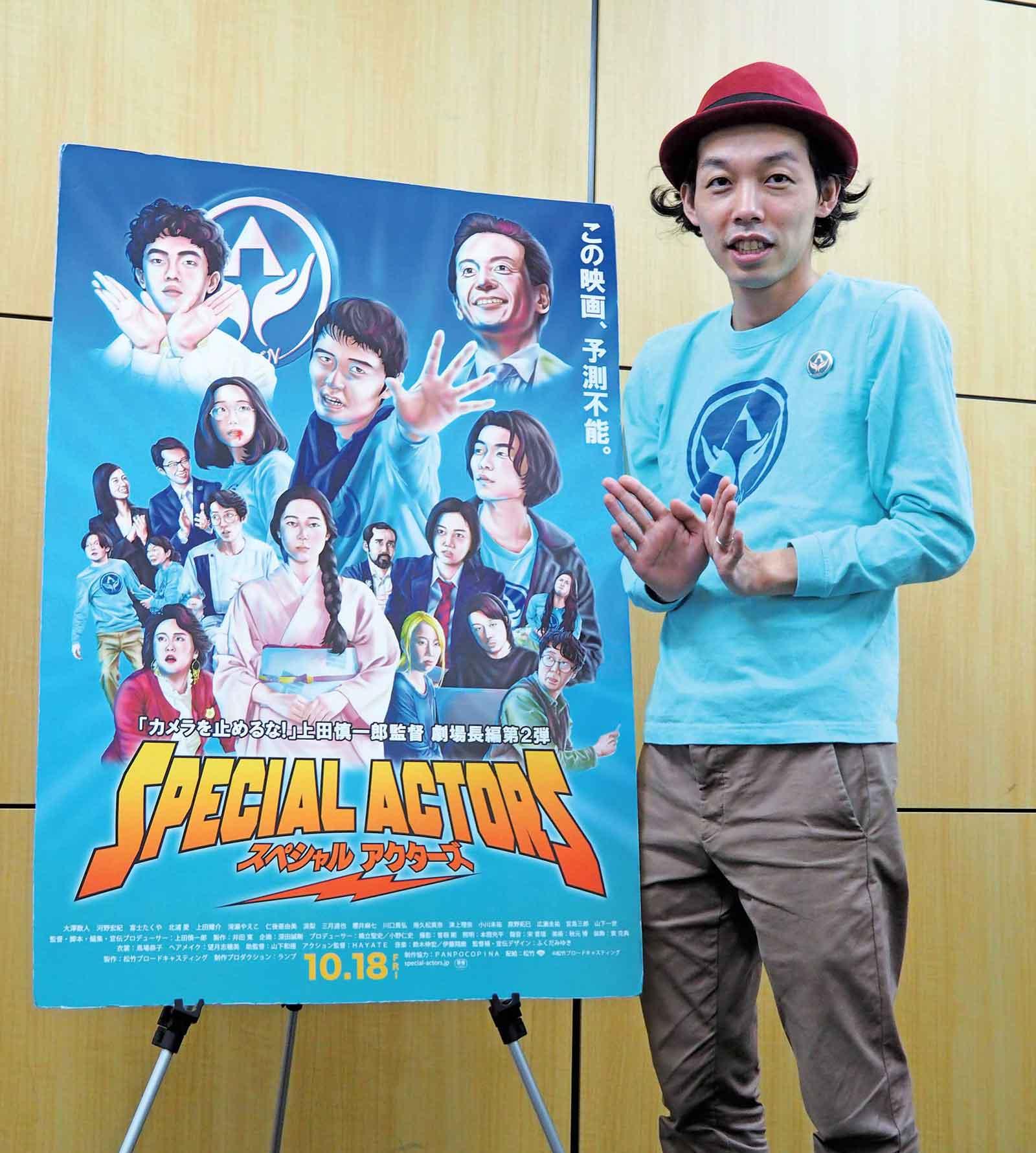 『スペシャルアクターズ』日本版劇場公開ポスターと上田慎一郎監督。このポーズと水色ロングTシャツの意味するところは、映画を見てのお楽しみ。